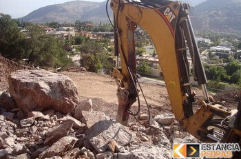 Desmonte de rochas em Santa Bárbara do Monte Verde com escavadeira hidráulica (picão)